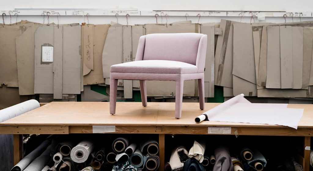 pink textile upholstered chair displayed on table