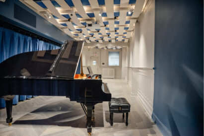 blue acoustic panels on ceiling in open room with piano in foreground