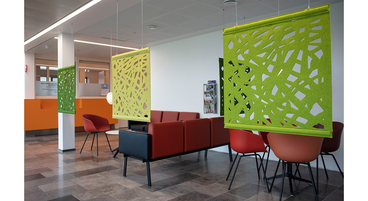 three wool felt screens with designs cut out hanging in an open office area