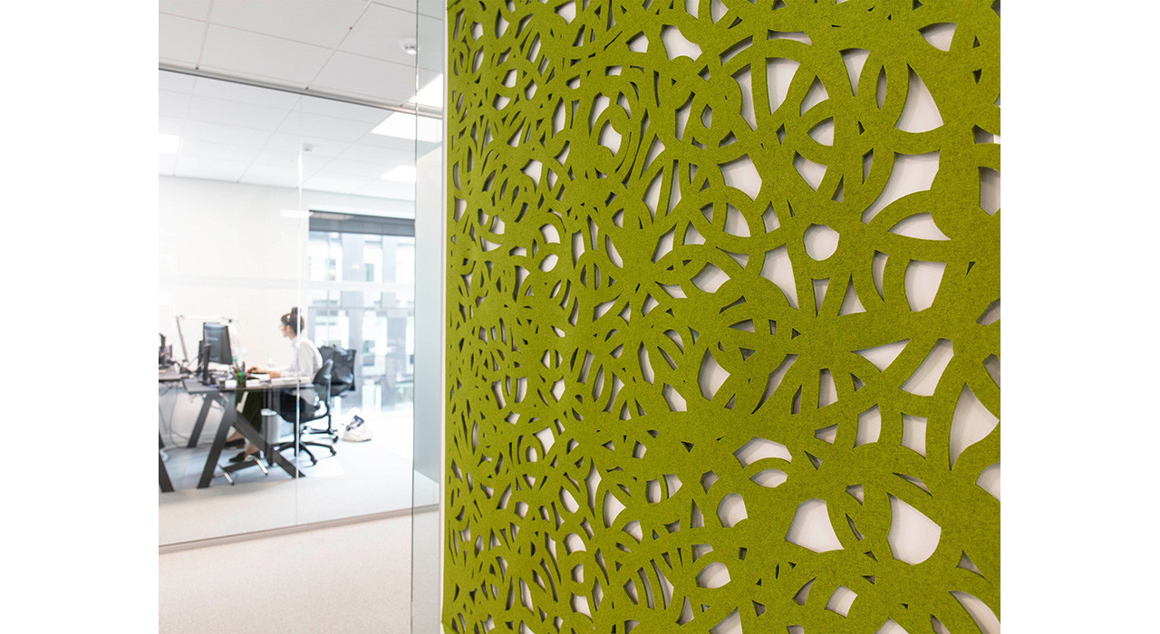 detail of an acoustic green wool felt screen with shapes cut out on office wall