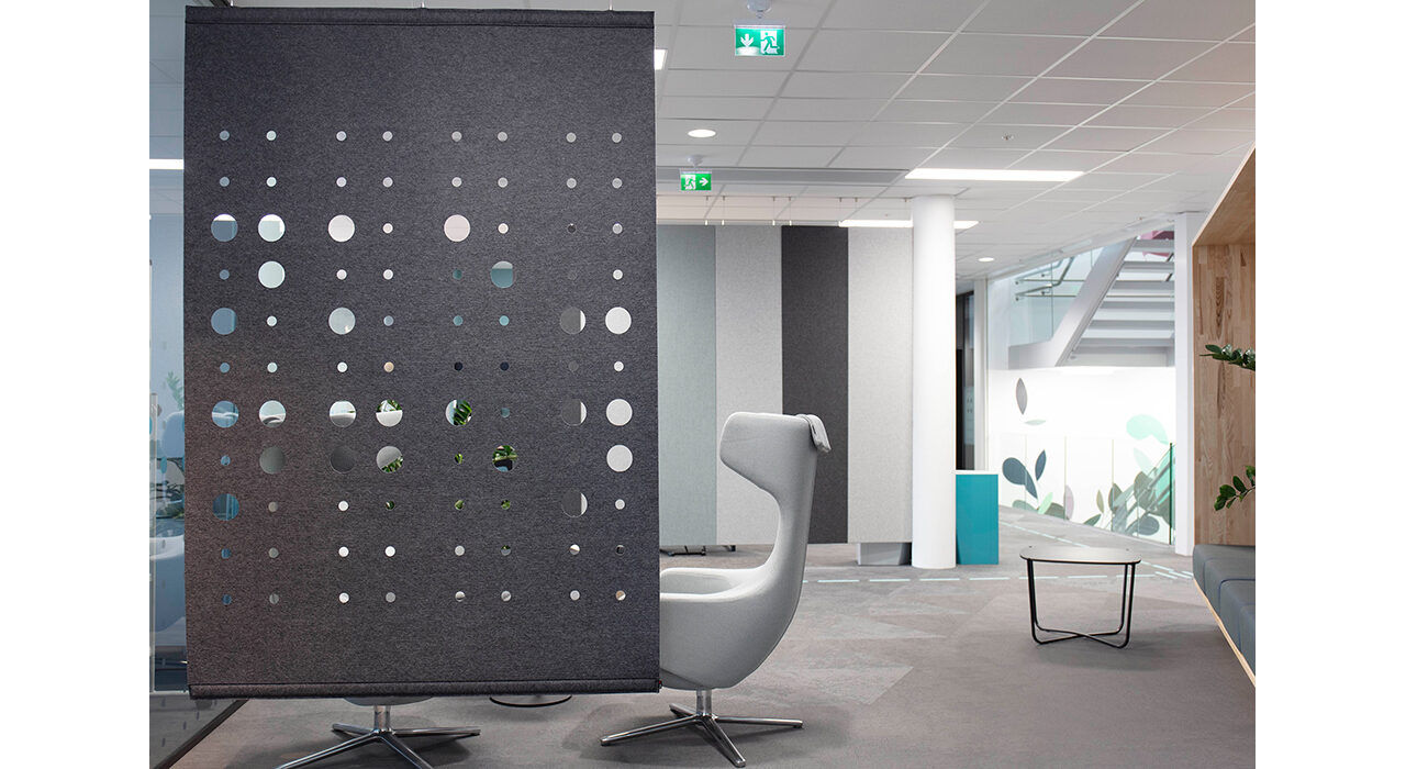 grey felt screen with circles cutout hanging in office