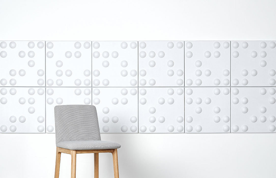 Installation featuring acoustic Ecoustic Bond White panels sound absorbing felt textile chair wall display
