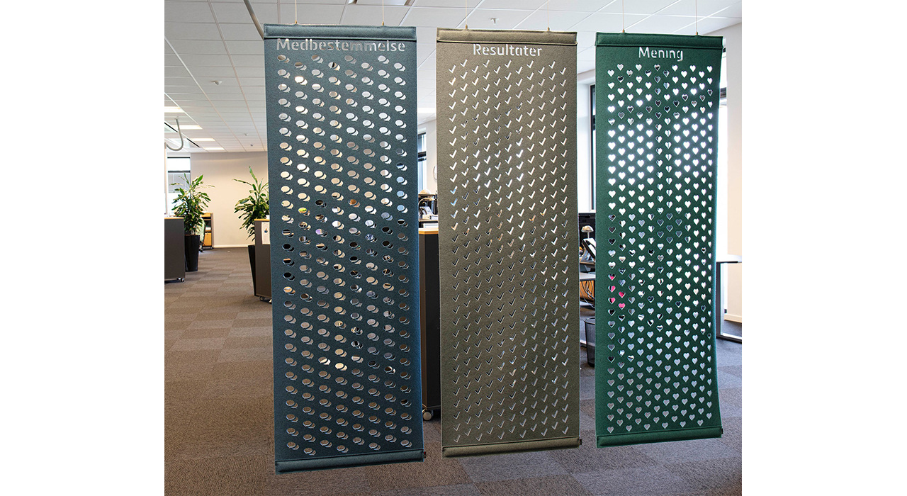 three felt screens with cutout designs hanging in office
