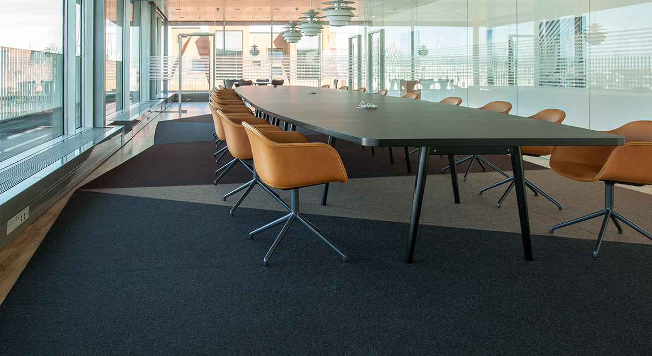 large felt rug under conference table and chairs in open office