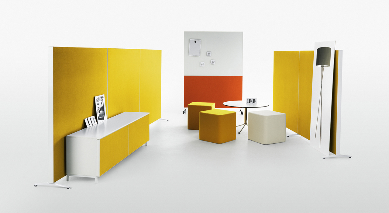 Installation featuring acoustic Alumi Screen yellow orange workspace office table desk sound absorbing