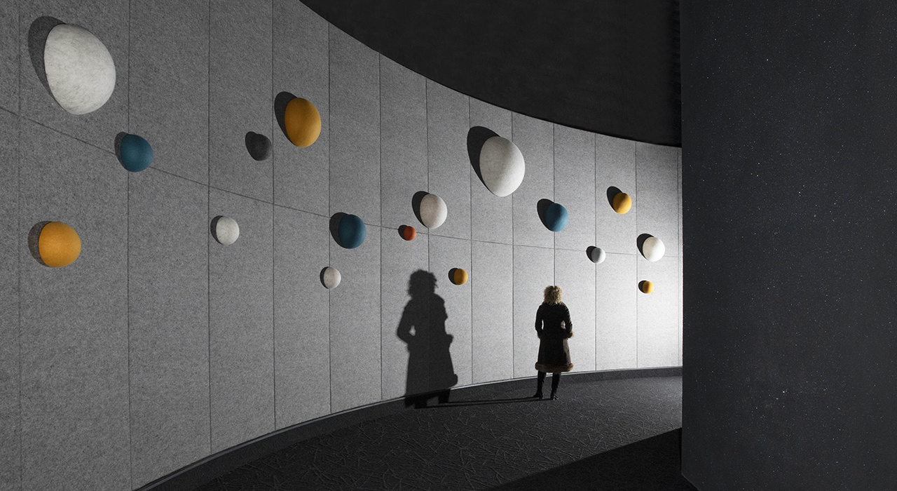 acoustic spheres on wall with person walking casting shadow