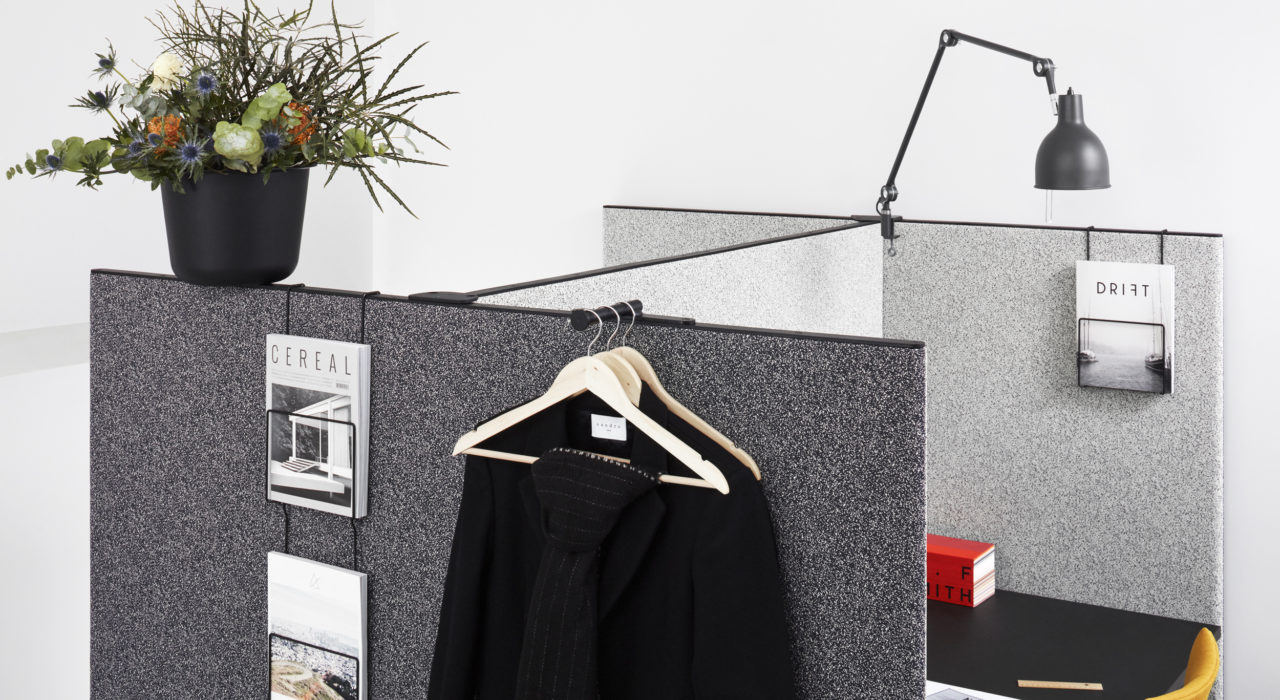 sound absorbing screen acoustic partition dB in charcoal with desk plant and lamp coats on hanger