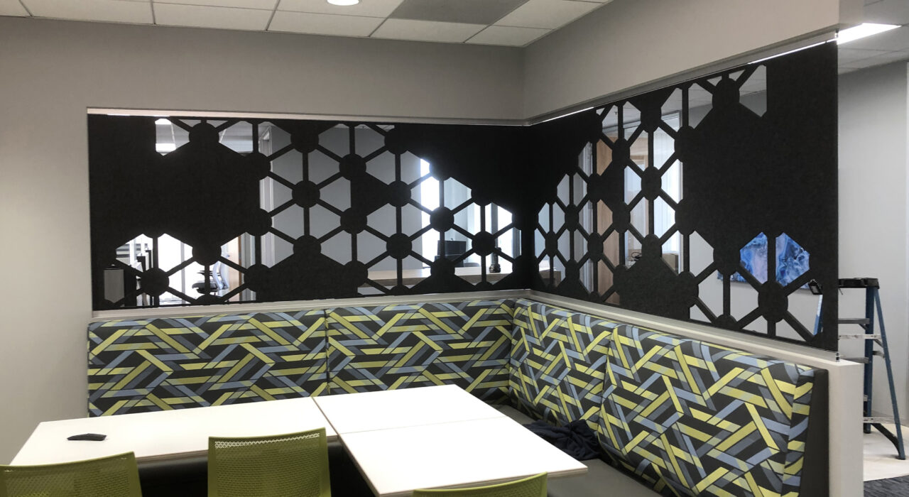 dark grey acoustic panel behind bench with table and chairs