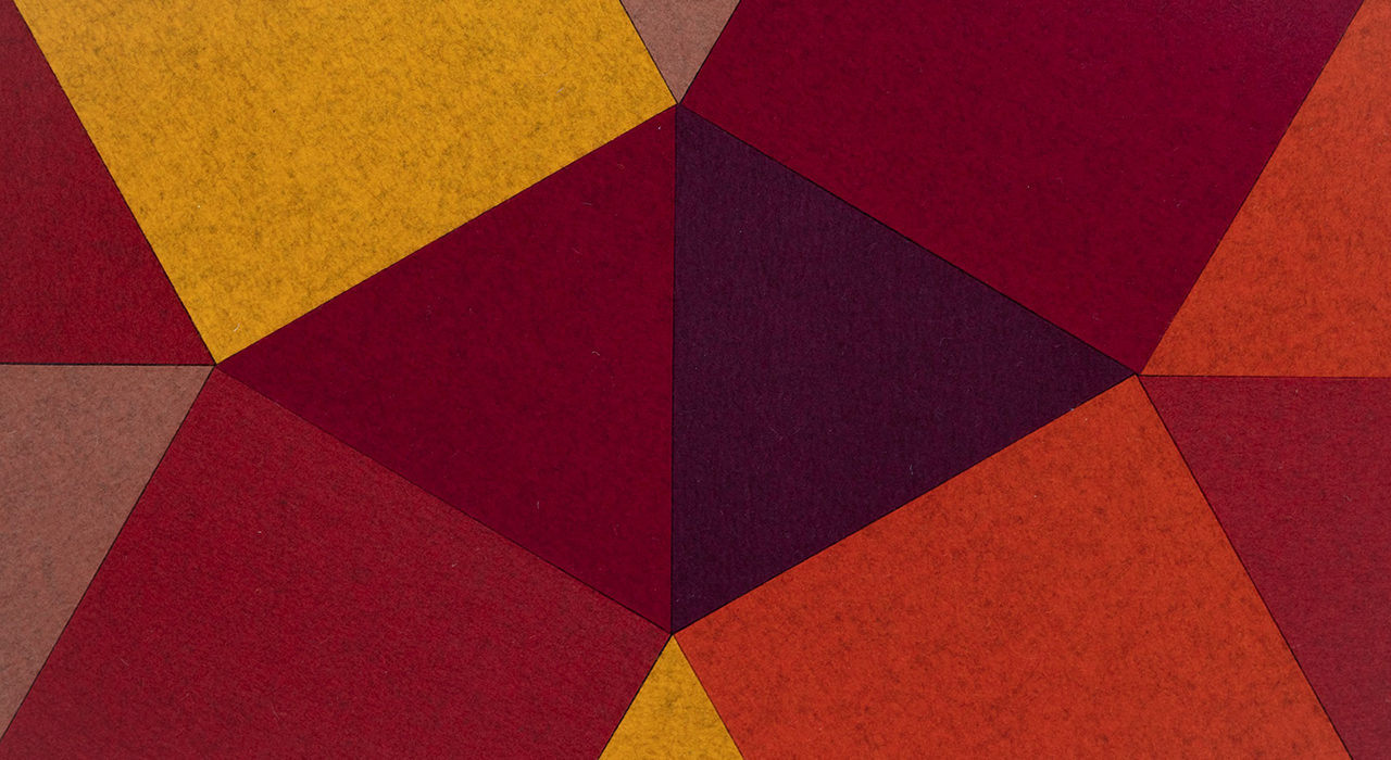 cut felt shaped acoustic tiles in red orange yellow and maroon grouped together closeup