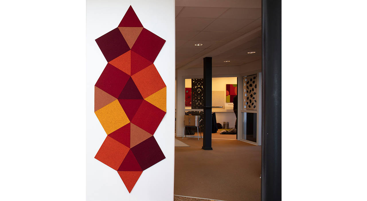 cut felt shaped acoustic tiles in red orange yellow and maroon grouped together looking down a hall