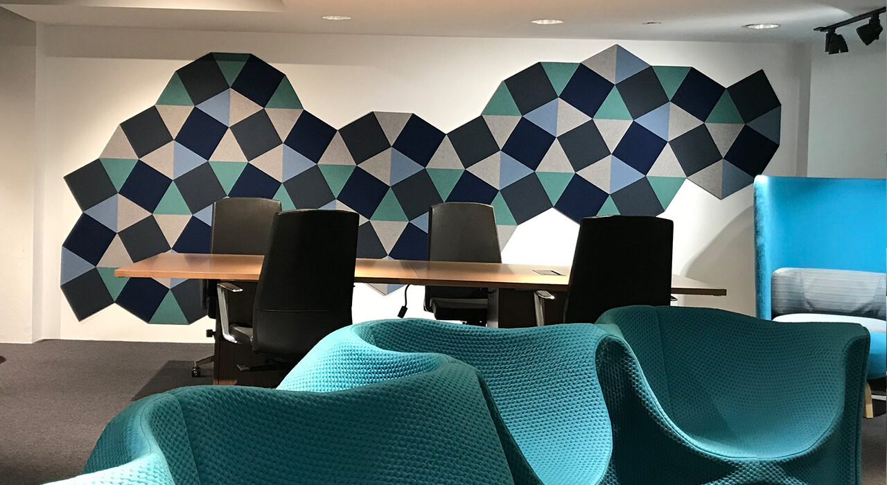 blue green and tan acoustic shapes on wall behind conference table