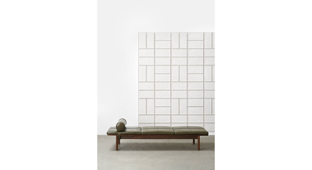 rectangular acoustic wall tiles on white wall behind a daybed