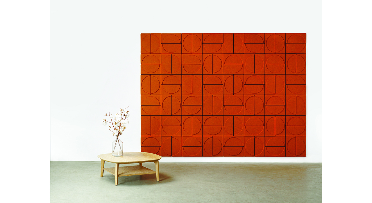 orange acoustic tiles on wall with coffee table and flowers