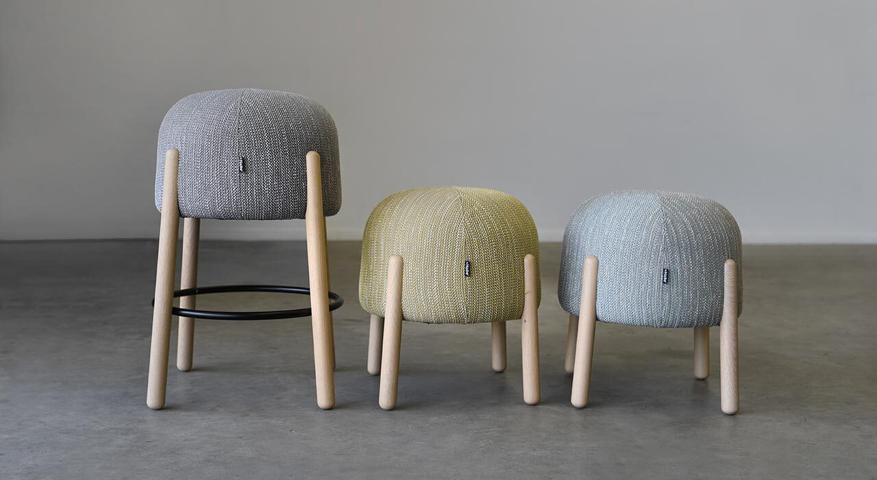 three stools in an open room upholstered in colorful textiles