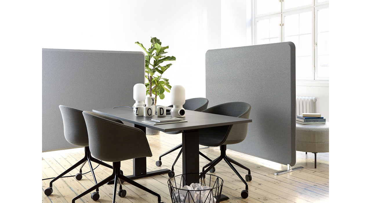 table and chairs with plant centerpiece surrounded by grey floor screens
