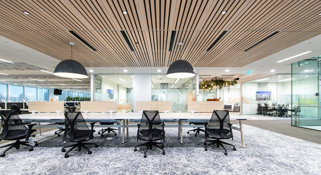 wooden ceiling panels in conference room above large table with black chairs