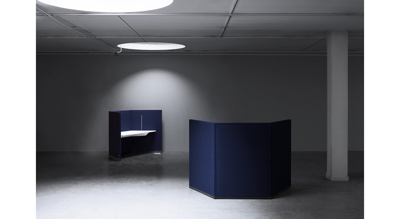 two blue acoustic workstations in a dark room with lights above