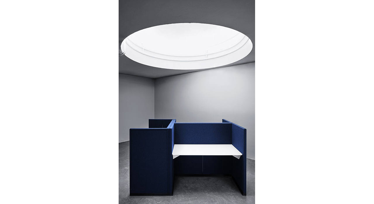 blue acoustic workstation with table attached and large light overhead