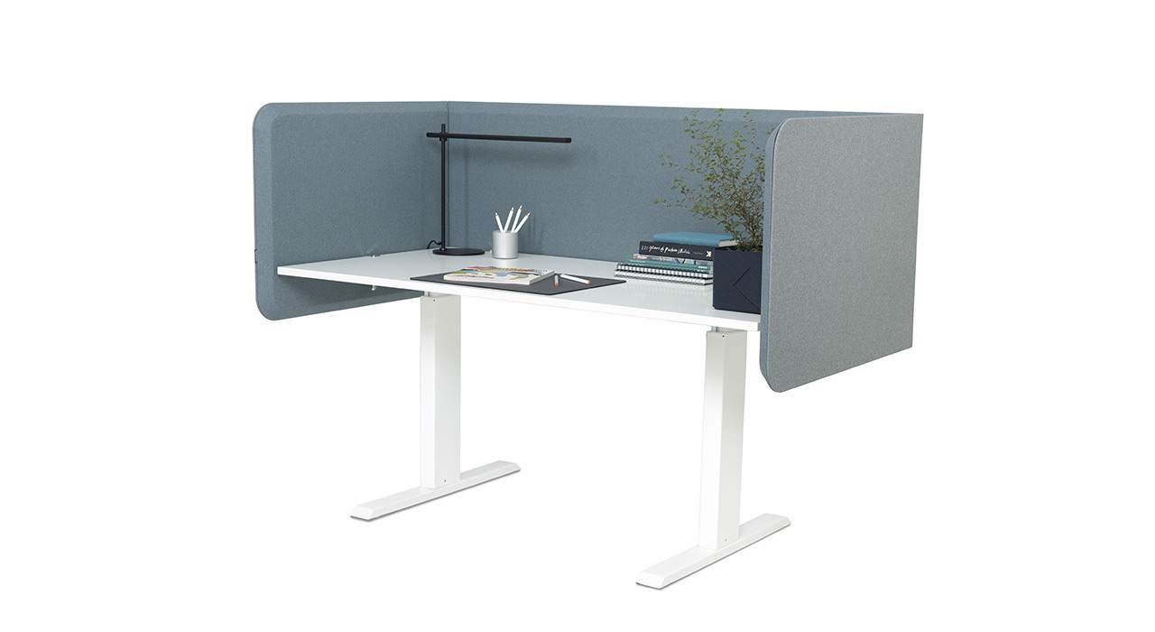 fully surrounded acoustic table screen at desk with plant and lamp