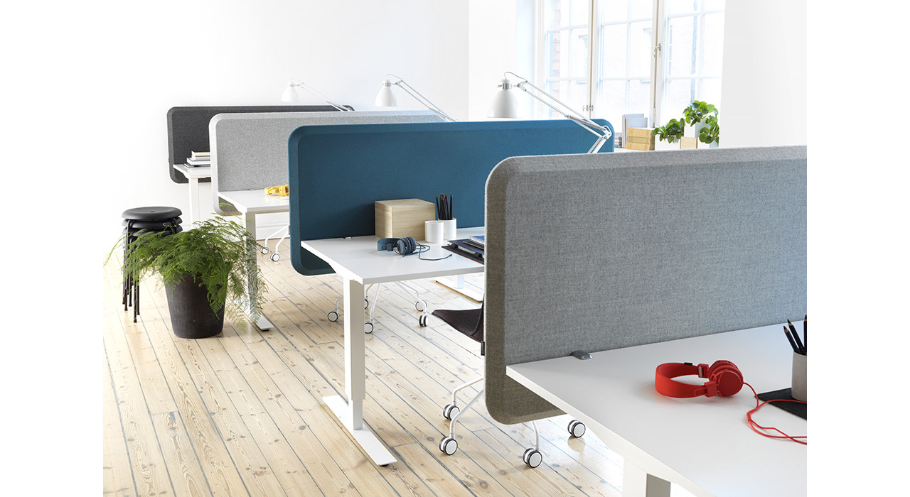 several colorful acoustic table screens on desks in office