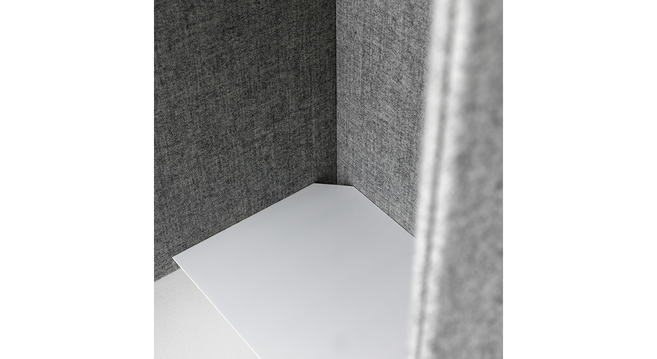 detail of grey sound absorbing booth with white shelf