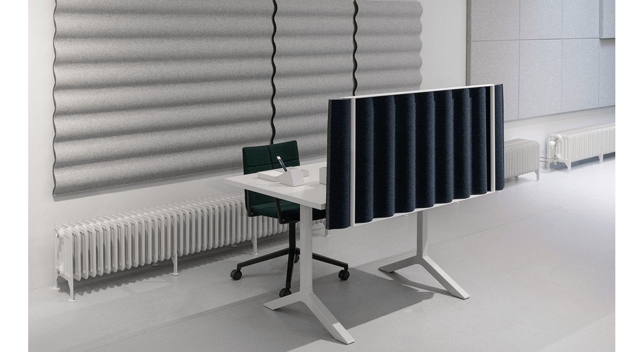 desk with acoustic table screen by window