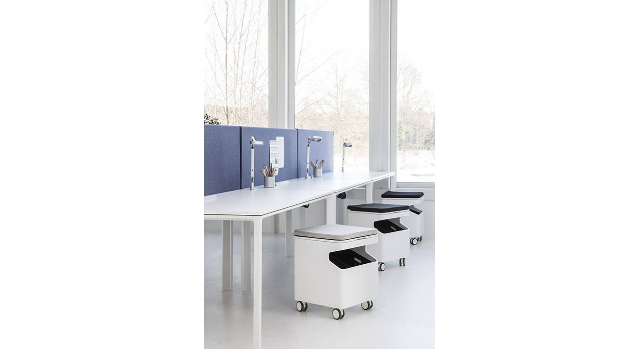 light blue acoustic table screens on white desks in office large window behind