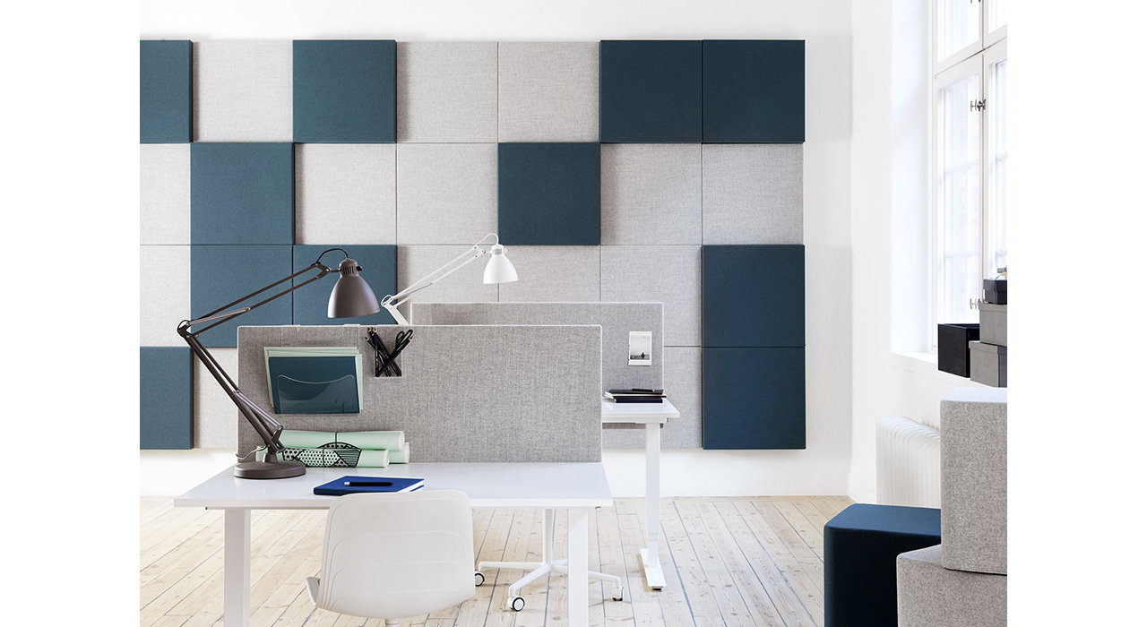 grey acoustic screens on white tables in office with sound absorbing wall tiles