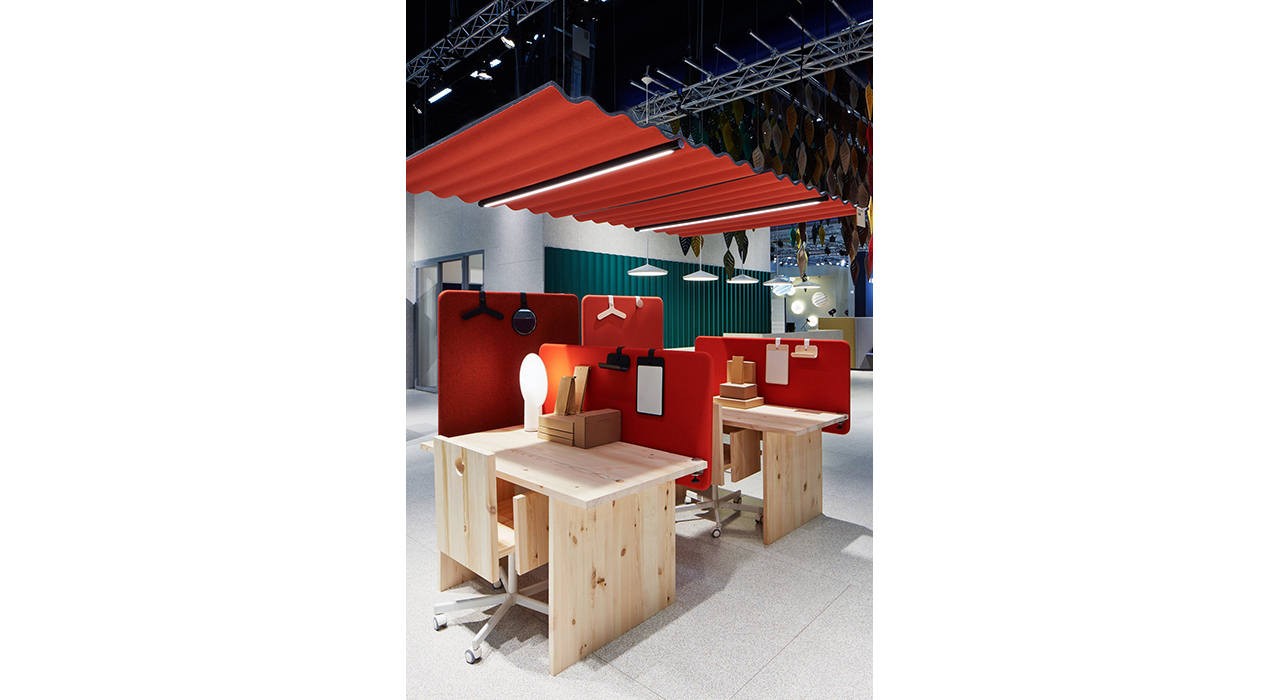 red ceiling tile above wooden desks with acoustic floor screens in showroom