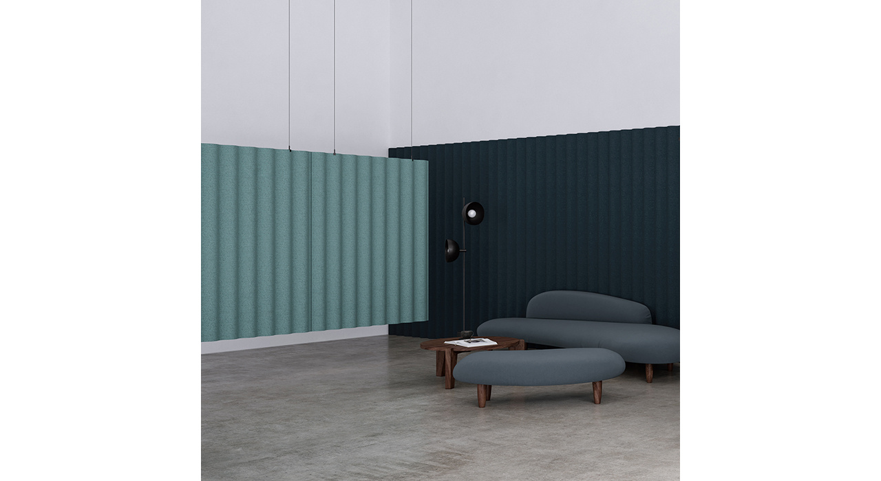 open room with green sound absorbing hanging screen and lounge seating