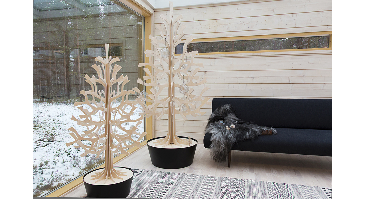 two wooden spruce trees next to large window and sofa