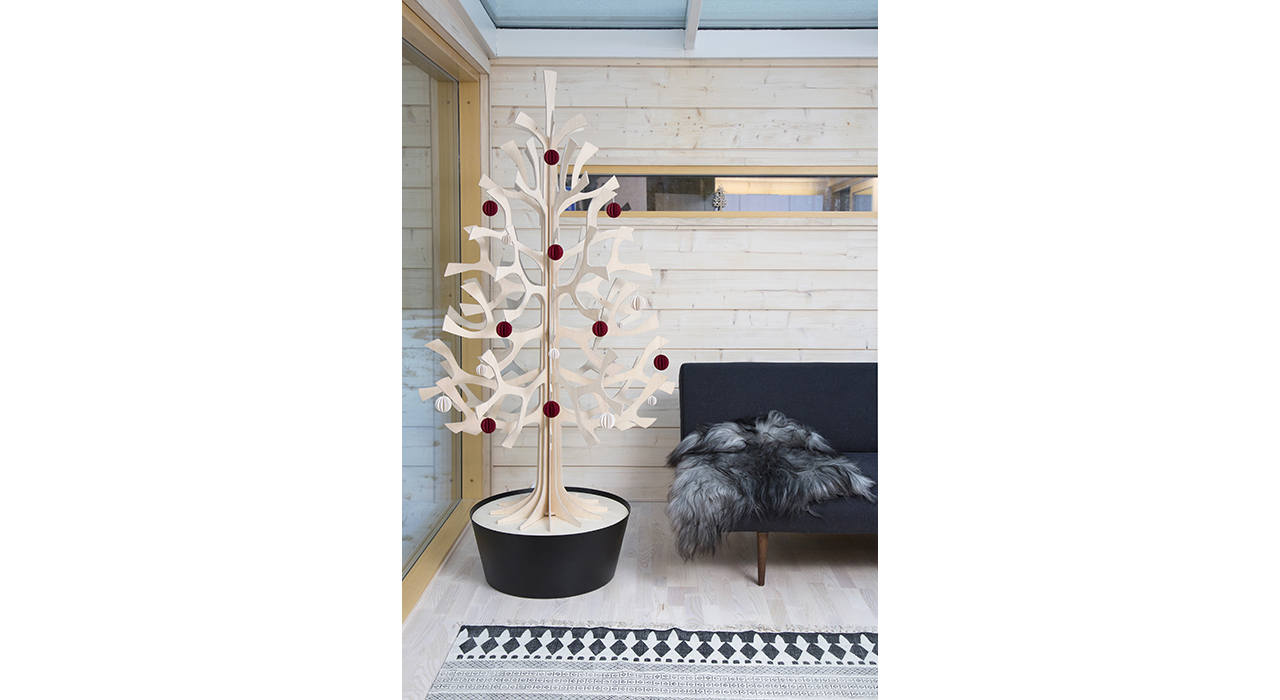 wooden spruce tree in black pot with red ornaments next to sofa