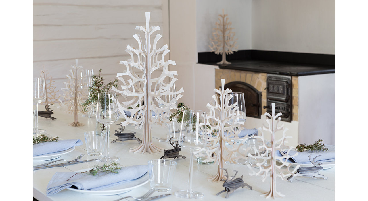 holiday table setting with small wooden spruce trees as centerpieces