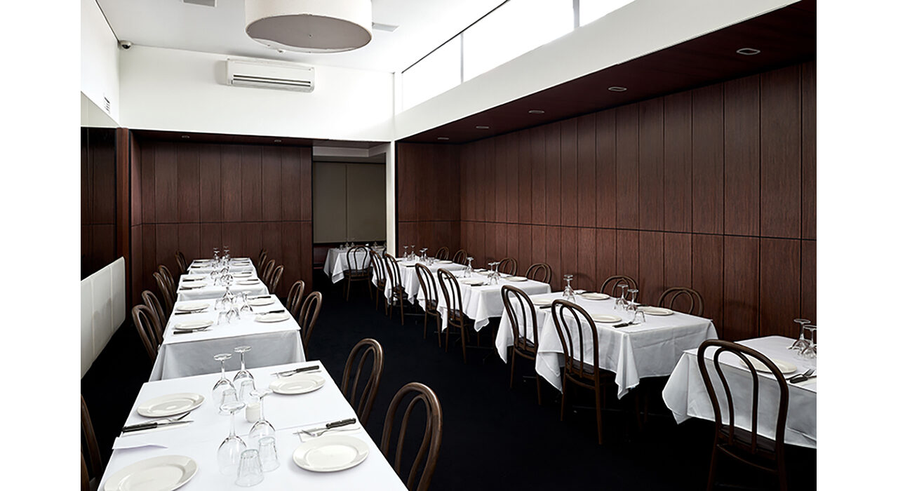 sound absorbing dark wood panels on wall with tables and chairs