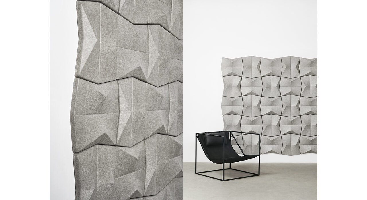 detail of grey sound absorbing tiles on white wall with black chair in foreground