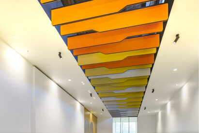 detail of orange yellow and white baffles above office reception area