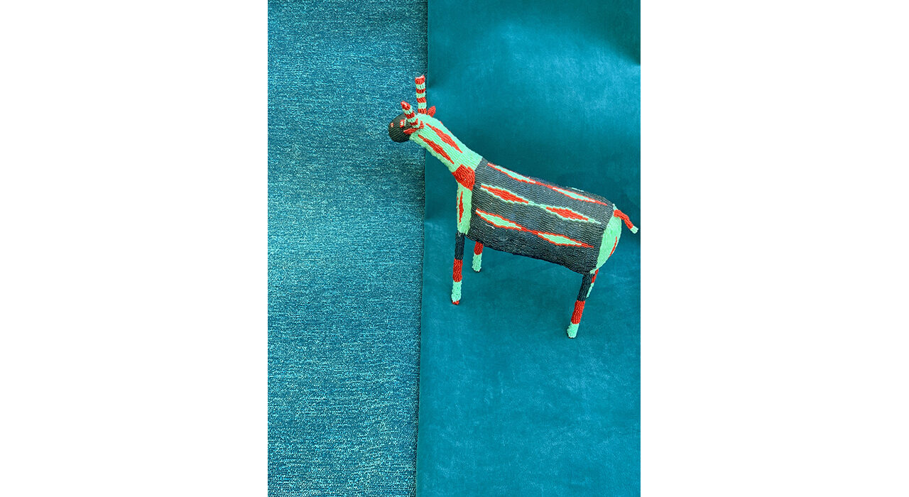 toy gazelle standing on two pieces of blue folded fabric