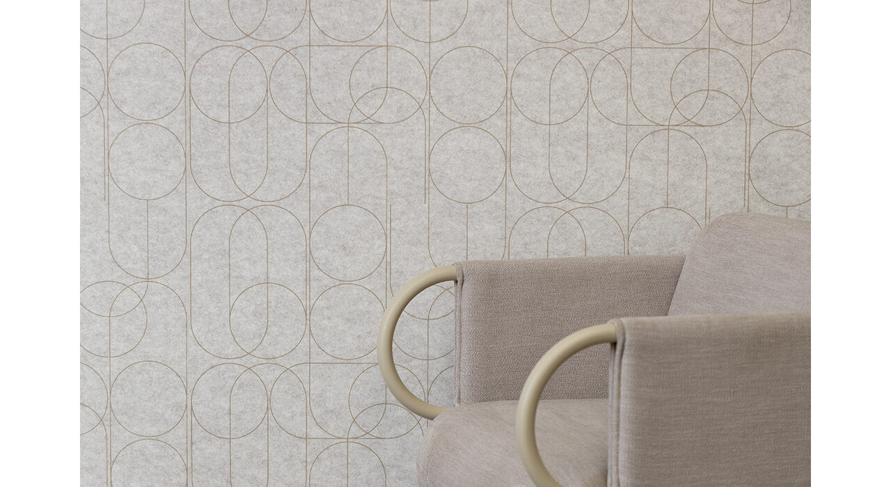 tan acoustic panel with printed pattern behind upholstered chair