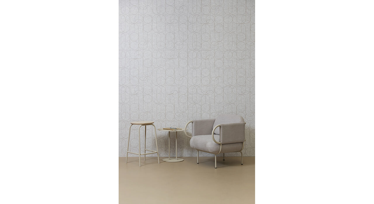 neutral sound absorbing wall panel behind upholstered chair with end table and stool