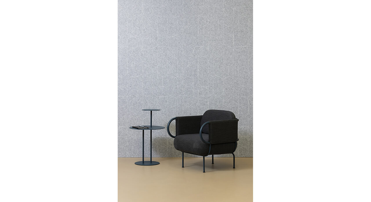 grey sound-absorbing acoustic panel on wall behind black upholstered chair and table