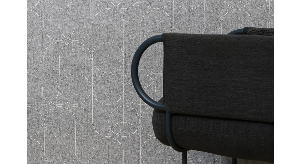 detail of grey acoustic panel with white pattern printed behind black chair