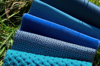 assorted blue textiles on grass by water