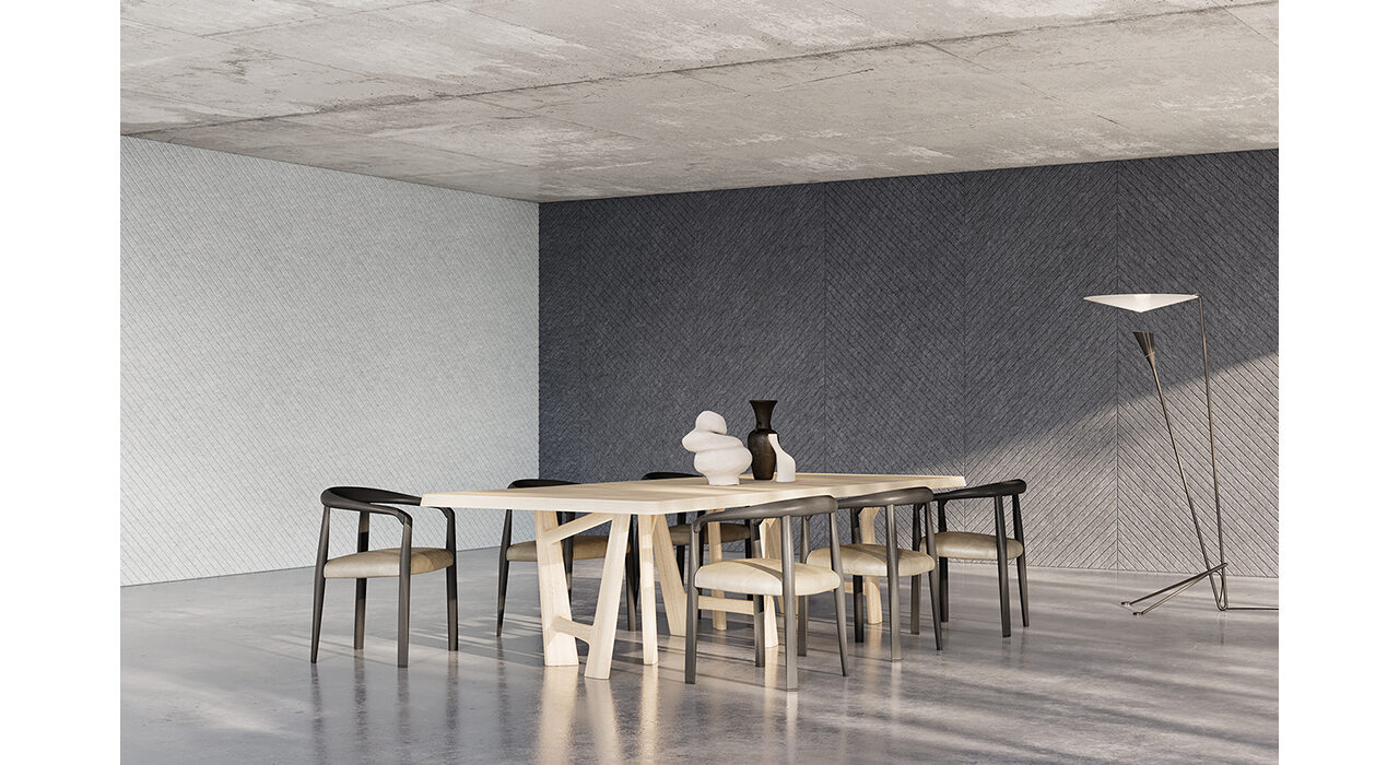 dark grey sound-absorbing panels on wall behind table and chairs