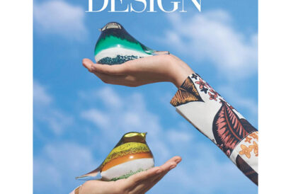 magazine cover with two hands holding decorative birds