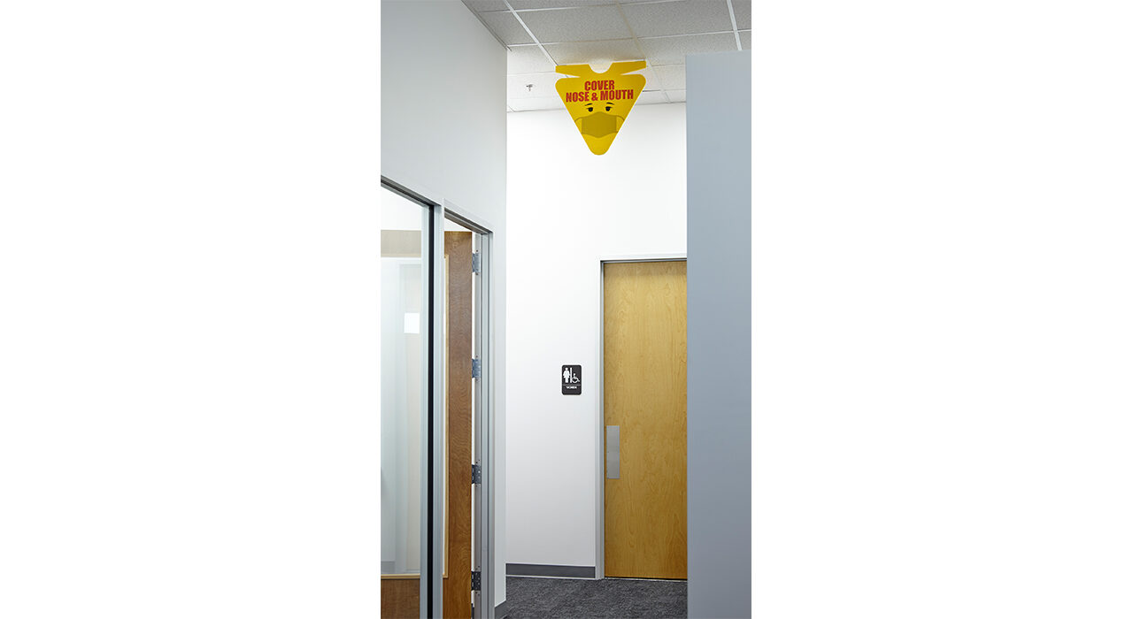 yellow cover mouth nose sign in office hallway