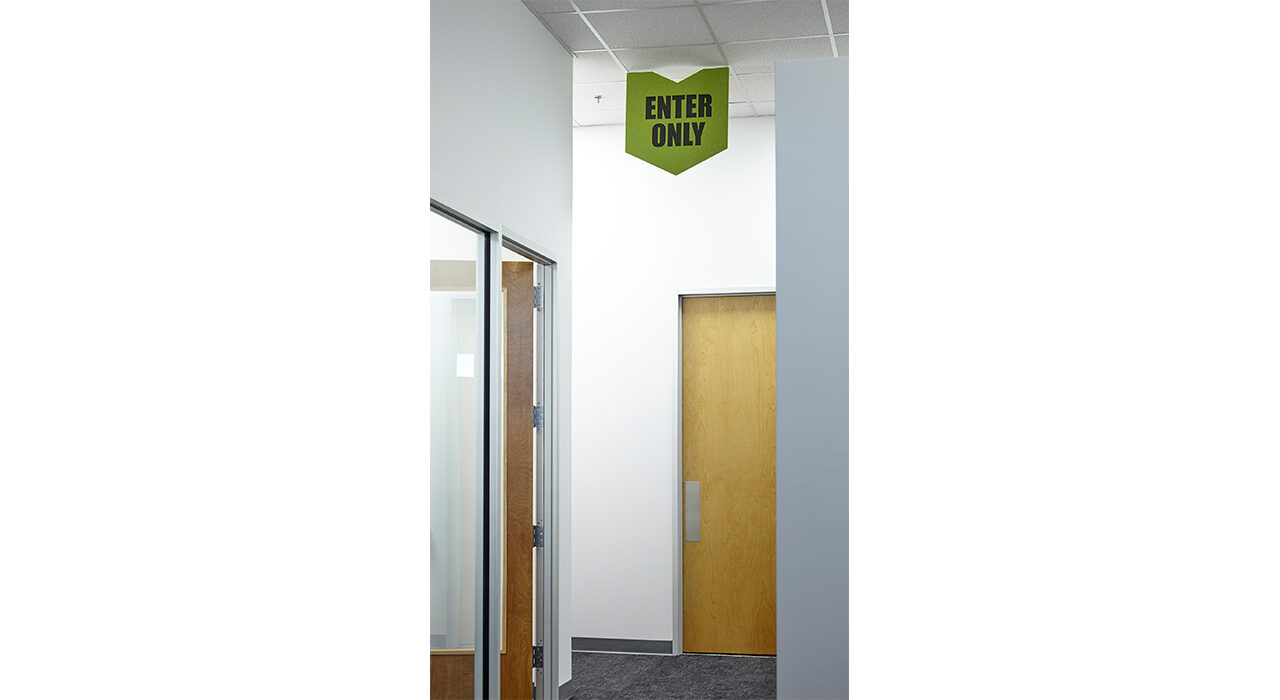 green enter only sign in office hallway