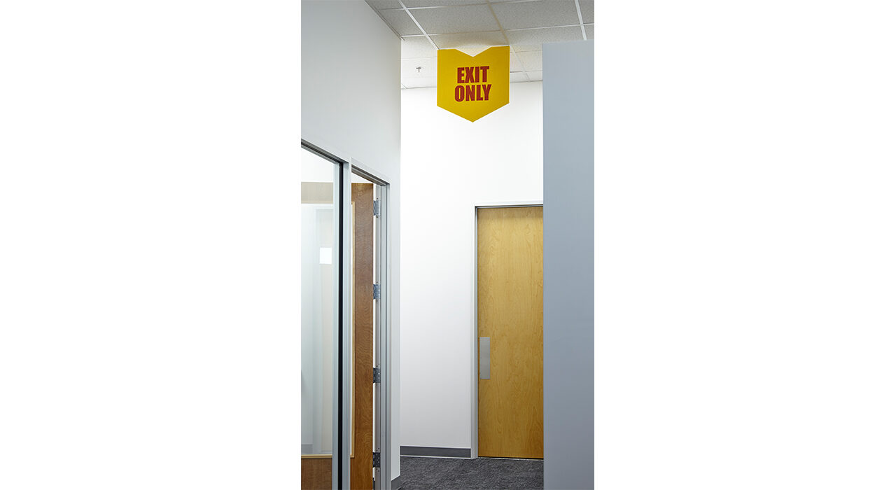 yellow exit only sign in office hallway