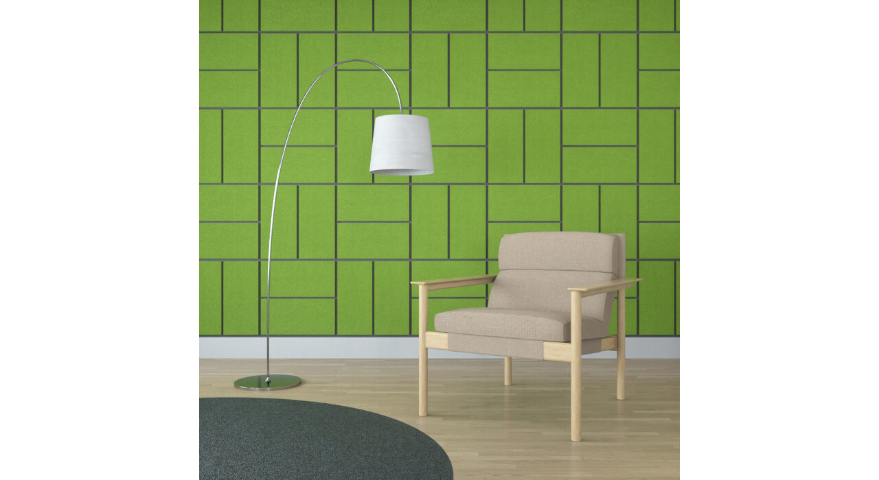 green rectangular shaped sound absorbing self stick tiles on wall behind chair